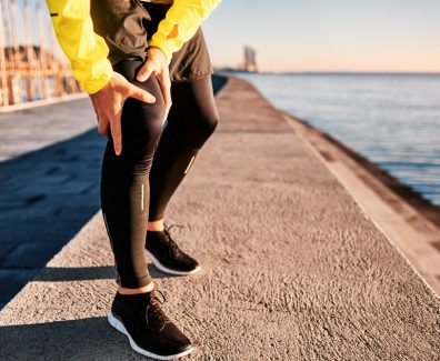 Knee Injury – sports running knee injuries on man. Close up of legs, muscle and knee outdoors. Male fitness athlete runner with pain from sprain knee.