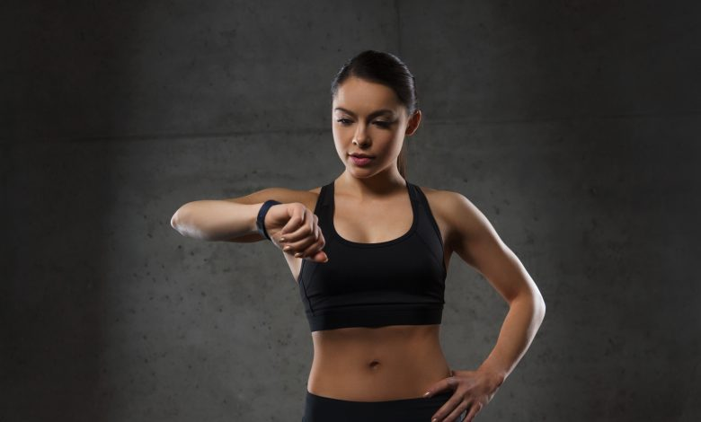 young woman with heart-rate watch in gym