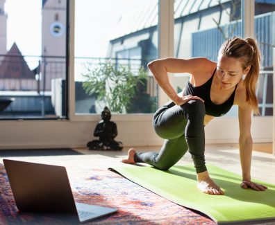 Woman exercising at home in front of her laptop, stretching her legs